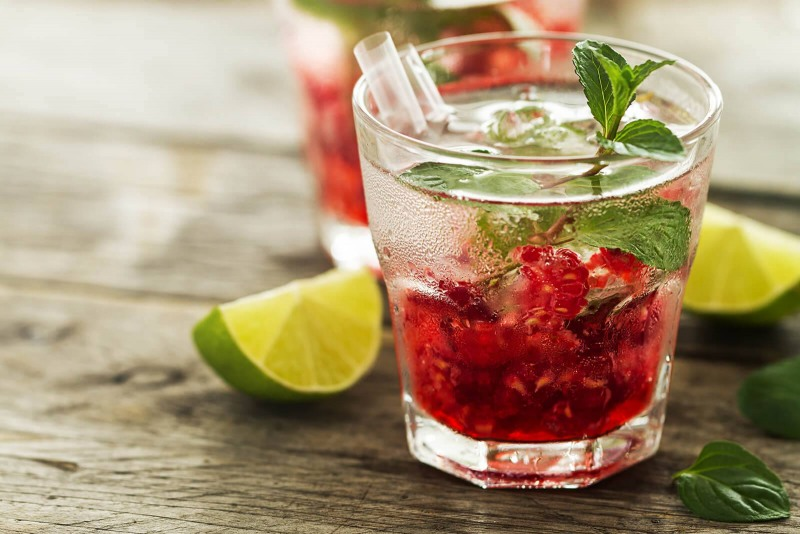 tasty-cold-fresh-drink-lemonade-with-raspberry-mint-ice-and-lime-in-glass-on-wooden-background-closeup